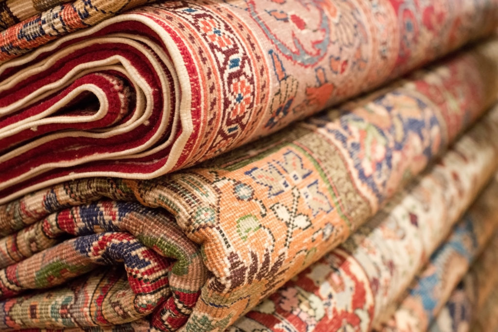 Bright various oriental rugs and carpets stacked for display.